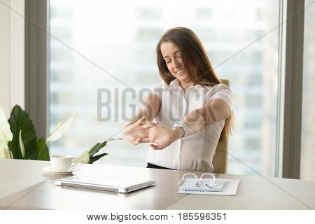 Happy businesswoman stretching wrists after her work done. Positive female office worker relaxing muscles after finishing job. Girl satisfied successful working day. Gymnastics at workplace concept