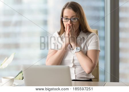 Surprised businesswoman looking at laptop screen. Pretty girl suddenly puzzled with e-mail or news in Internet. Young female office worker looks shocked after computers critical failure