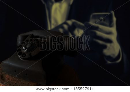 Black classic phone on a man hand typing on smartphone,Black antique vintage analog telephone dialing or scrolling phone on wooden table,Contact us concept.