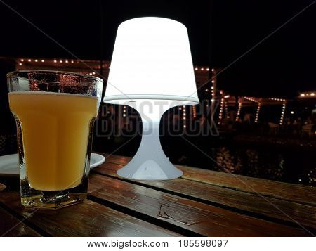 Classic lamp and light beer at the bar on night background,Beautiful background of the Oktoberfest,Glass of cold fresh lager beer on a wooden table in pub with free space for your text,Soft focus.