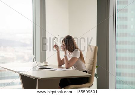 Exhausted businesswoman sitting in front of laptop at the large modern desk and massaging nose bridge. Frustrated female entrepreneur feeling weakness while working in office. Fatigue after overwork