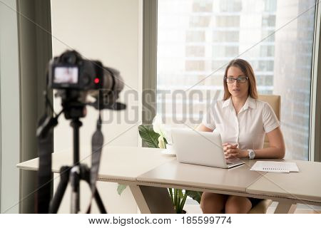 Confident businesswoman sitting at desk in front of laptop and looking at camera on tripod that records video. Female blogger makes footage for social networks. Woman recording videolog at workplace.