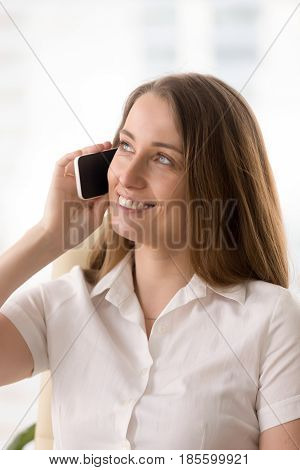 Smiling businesswoman has pleasant conversation on cellphone. Happy lady talking on mobile phone with interest. Successful female entrepreneur calling colleagues. Woman glad to hear good news by phone