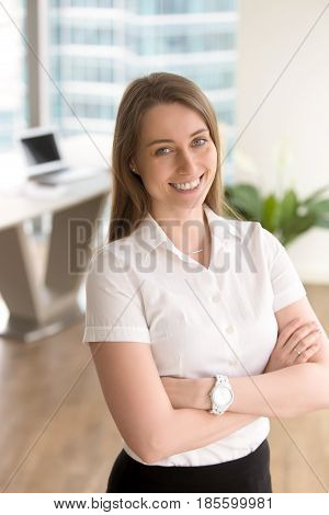 Happy young woman standing with arms crossed in office interior and smiles broadly. Successful businesswoman satisfied with positive results. Female entrepreneur enjoys career impressive achievements