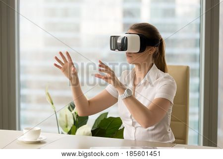 Businesswoman in VR headset interacting with virtual objects or interface while sitting in armchair at the table in office. Young girl making virtual business presentation with virtual reality glasses