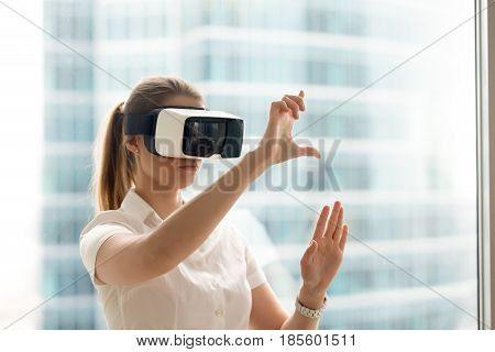 Beautiful girl using virtual reality glasses near bright window with skyscraper view outside. Business woman wearing VR goggles and interacts with cyberspace using swipe and stretching gestures