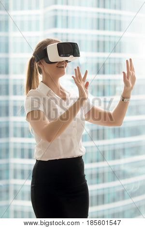 Young woman in formal clothes enjoying virtual tour or excursion with VR headset. Girl in virtual reality glass standing near bright window and touching objects in virtual or augmented reality