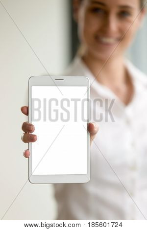 Close up photo of digital tablet in hand of smiling woman. Woman shows new model of portable computer with blank mock up screen with copy space. Female presenting technology innovation, trendy device
