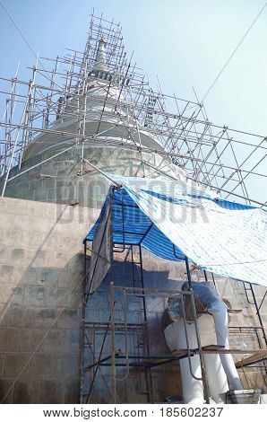 Large Temple Stupa under construction and surrounded with scaffolding.