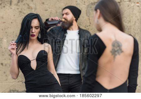 Adorable girl smoker with sexy red lips makeup smoking cigarette. Blurred pretty woman in black dress with tattoo on back and bearded man drinking wine from bottle. Unhealthy habits and lifestyle
