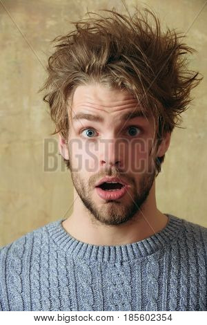 guy or handsome bearded man with beard or sexy caucasian surprised macho on beige wall background. Stylish blond hair haircut and young unshaven face skin. Male beauty and hairdressing.