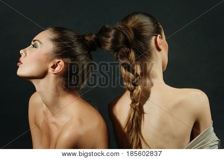 naked sexy women or pretty girls lesbian models with braided or tied beautiful healthy brunette long hair into braid or plait on dark background. Friendship and love