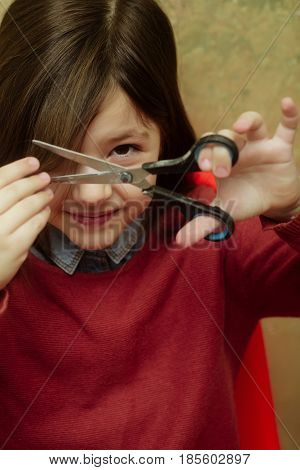Adorable Girl Cutting Hair With Scissors