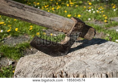 Old used weathered worn grunge metal ax stuck in wooden log closeup on rural background