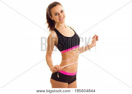 smiling sports girl in top and shorts takes the waist measuring tape isolated on white background