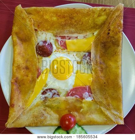 Top view of delicious crepe with bologna sausage cheddar cheese egg and salami served on a white plate on a red service napkin