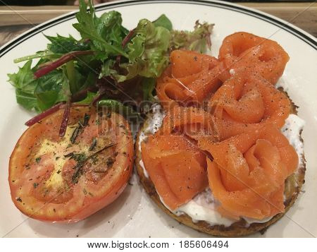 Closeup healthy cold appetizer, hash brown with garlic cream cheese and smoked salmon on top garnish with herb,serving side dish with green lettuce and tomato salad,focus-on-foreground blur background