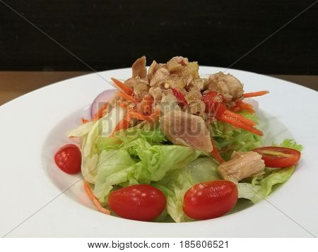 Healthy Tuna salad with lettuce tomato and light vinegar dressing in white plate on wooden tablestylist fusion foodblack isolate background focus-on-foreground blur backgroundclosed up