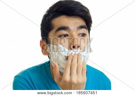Portrait of a ridiculously young guy that does shaving foam on your face closeup isolated on white background