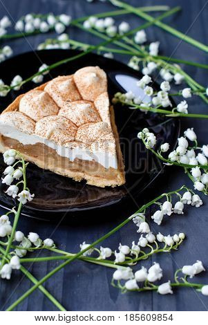 Apple tart with sour cream. Apple pie with meringue and lilies of the valley. Apple pie from short pastry with whipped cream. Fruit pie on a dark background.