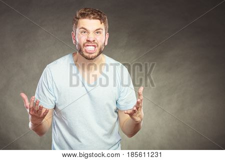 Portrait of upset angry mad man in shirt. Young guy in studio on black. Face expression.