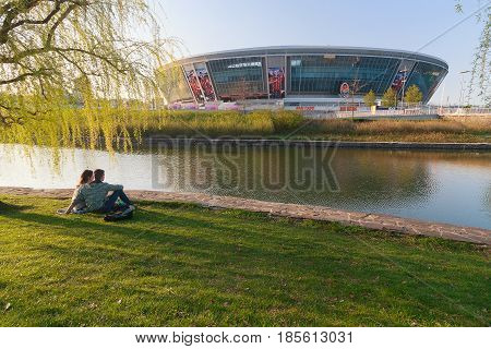 Donetsk Ukraine - April 29 2017: Young couple is resting in a park near the Donbass Arena Stadium