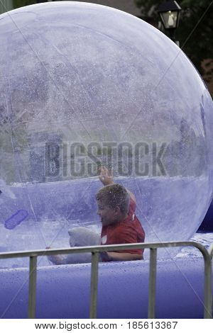 Cornwall, Quebec - July 26, 2014 - Vertical of a young boy playing inside large plastic bubble in a pool at the Ribfest in Cornwall, Ontario on a sunny afternoon in July.