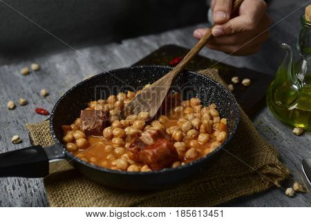 a frying pan with potaje de garbanzos, a spanish chickpeas stew with chorizo and serrano ham, on a rustic wooden table