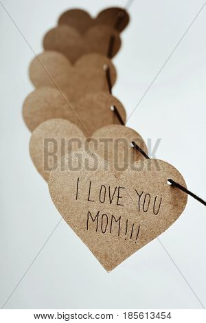 closeup of some brown cardboard hearts strung on a string and the text I love you mom written in the first one, against an off-white background