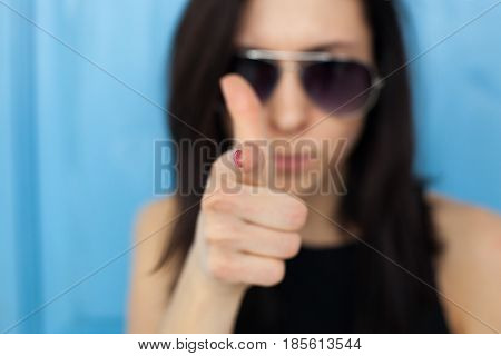 Blurred Portrait Of A Girl In Sunglasses. She Points To The Index Finger, Pointing To The Viewer.