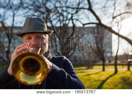 An Elderly Musician Plays In The Street On A Trumpet In Spring Day