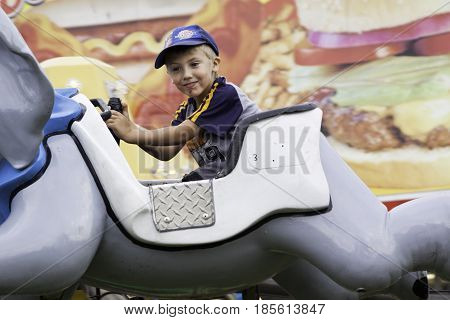 Cornwall, Quebec - July 26, 2014 - Wide view of a young boy enjoying a carnival fun ride at the Ribfest in Cornwall, Ontario on a sunny afternoon in July.