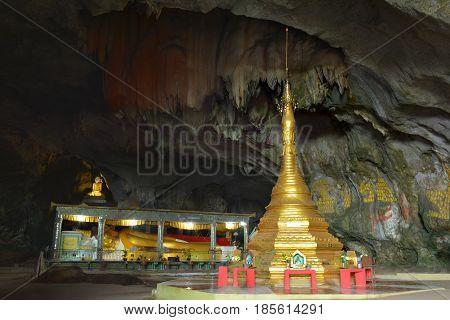 Beautiful view inside sacred Sadan Cave Myanmar (Burma). Ancient golden stupa and big lying Buddha statue inside.