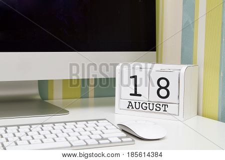 Cube shape calendar for AUGUST 18 and computer with white screen on table.