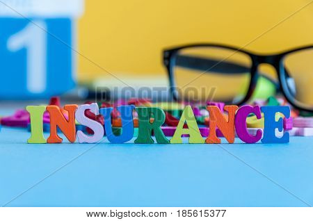 Insurance - word composed of small colored letters on business workplace of broker. Illustration of the concept of insurance.