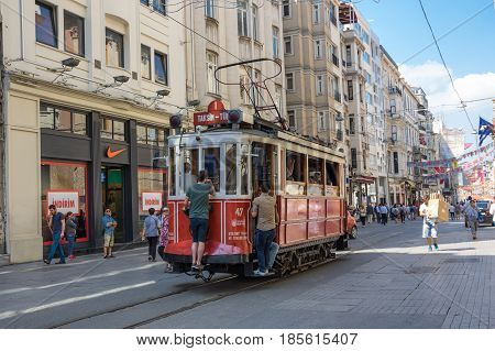 ISTANBUL TURKEY - JUNE 26 2015: A red classic tram in Istiklal street in the Beyoglu district of Istanbul Turkey. It is the most famous street in Istanbul