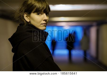 A Girl In Black Clothes Is Walking Along An Underground Passage. She Looks Back.