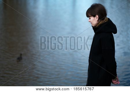 Portrait Of A Lonely Girl By The Lake. She Stands In Black Clothes And Looks Sadly Aside, I Think Ab