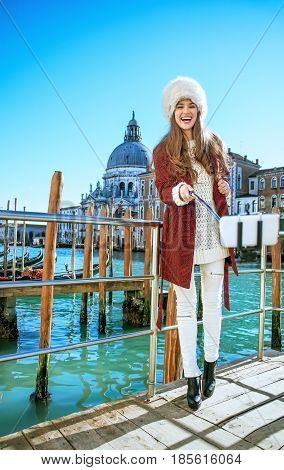 Woman On Embankment In Venice Taking Selfie Using Selfie Stick