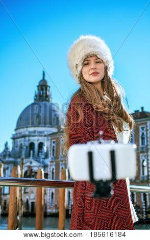 Woman On Embankment In Venice Taking Selfie Using Selfie Stick