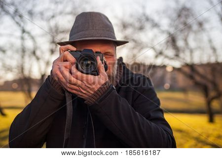 A Mature Man In A Hat Takes Pictures On A Mirrorless Camera In The Street. Hobby Of Photography. New