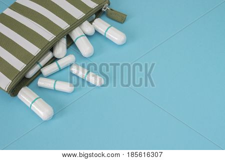 Stripe beautician with Menstruation soft clean cotton sanitary tampons. Travel cosmetic bag on the blue paper. Hygiene protection for woman critical days