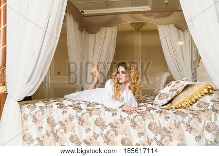 Beautiful seductive woman flirting with the camera lying on the bed with in White bathrobe looking up with a coquettish look.