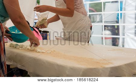 Homemade strudel dough on a traditional linen tablecloth ready for making cottage cheese pie and other pastry. The process of making pie dough according to the traditional Hungarian recipe. Women are spreading nuts and cottage cheese on a rolled dough