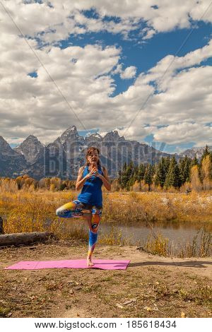 a woman practicing yoga in fall in the scenic Tetons of Wyoming