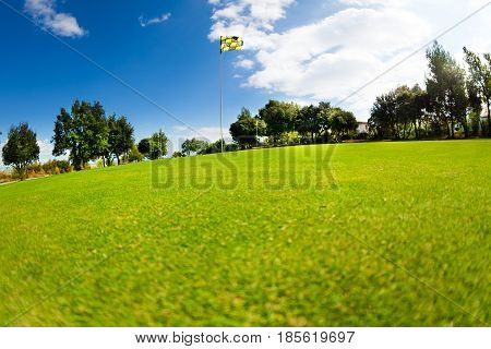 Beautiful scenery of green golf course with flagstick in the distance at sunny day
