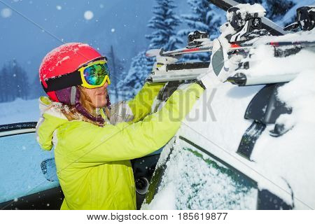 Portrait of female skier fastening skis to roof rails of the car after ski trip during snowfall