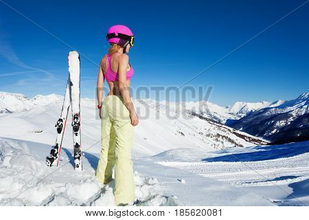 Back view picture of sporty girl in pink helmet with skis inserted into snow on a sunny day in the mountains