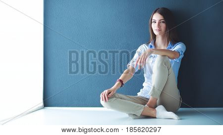 Young woman sitting on the floor near dark wall