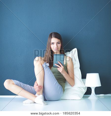 Portrait of a pretty brunette woman sitting on the floor with a pillow and plane table